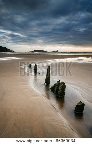 Landscape With Old Groynes Protruding From Sand On Rhosilli Bay Beach