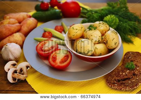 Young boiled potatoes with vegetables on table, close up