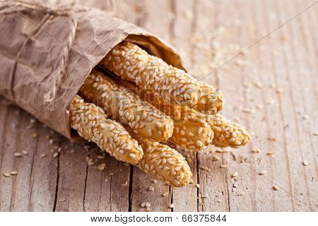 bread sticks grissini with sesame seeds in craft pack on rustic wooden background