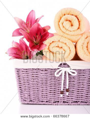 Color towels and lily flowers in wicket basket, isolated on white