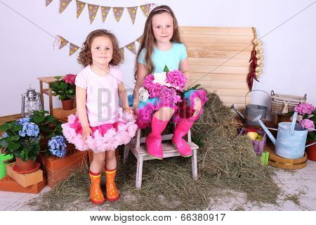 Beautiful small girls in petty skirts holding flowers on country style background