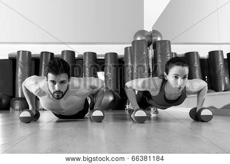 Dumbbells push-ups pushups couple at fitness gym workout