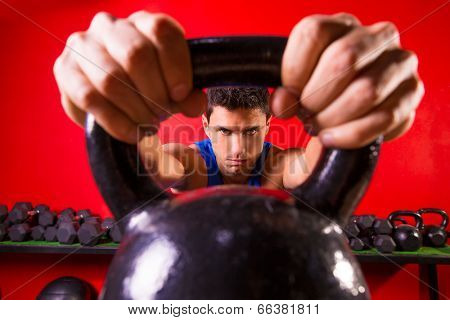 Kettlebell man portrait looking through the handle ring at gym workout