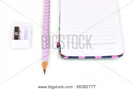 Pencil, pencil sharpener and notepad isolated on white