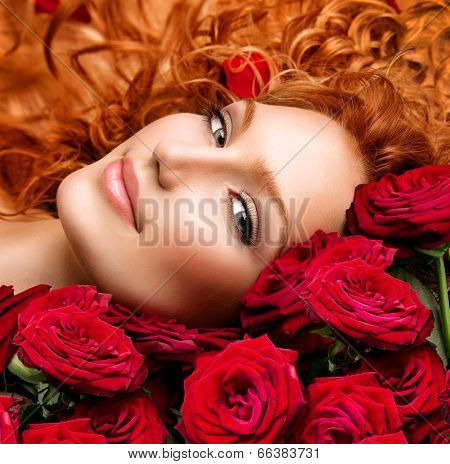 Beauty model girl with long curly red hair and beautiful red roses bouquet. Hairstyle with flowers. Fashion woman with Wavy healthy hair lying on beautiful roses. Permed hair