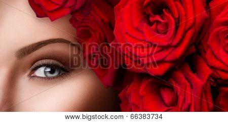Beauty eyes makeup. Close-up of beautiful woman blue eye with red roses and stylish make up