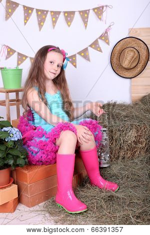 Beautiful small girl in petty skirt holding kerosene lamp on country style background