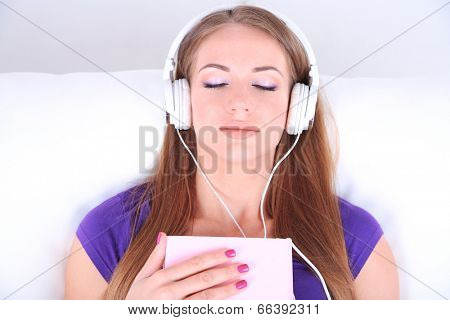 Conceptual image of  audio book.Beautiful girl with book and headphones.