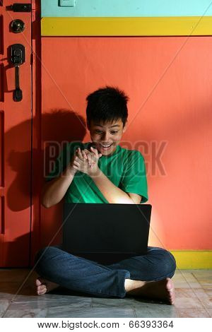 Young asian teen with a laptop computer in a living room