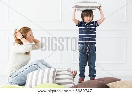 Cute, adorable boy with mother fighting with pillows
