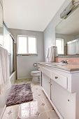stock photo of linoleum  - White bathroom with old vanity cabinet linoleum and soft rug - JPG