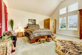 stock photo of vault  - Tropical bedroom with high vaulted ceiling decorated with tiger statues and rug - JPG