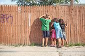 stock photo of peeking  - Kids peeking through a fence - JPG