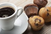 picture of chocolate muffin  - muffin with chocolate chips and cup of coffee on wooden table