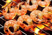 stock photo of charcoal  - Grilled shrimps on the flaming grill - JPG