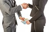 image of bribery  - Man gives woman money while shaking hands over a white background - JPG