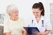 image of clipboard  - Young Female Doctor Writing On Clipboard Sitting With Senior Patient - JPG
