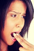 picture of vomit  - Woman putting her finger in her mouth to provoke vomiting  - JPG