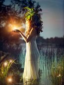 stock photo of witchcraft  - Fantasy girl taking magic light in her hands - JPG