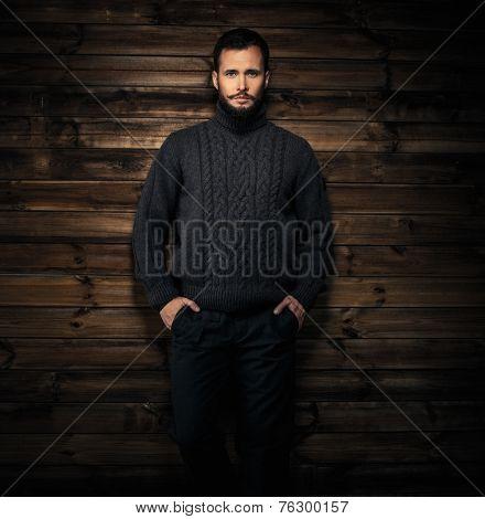 Handsome man wearing cardigan in wooden rural house interior