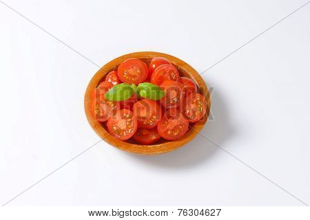 overhead view of bowl with halved cherry tomatoes decorated with basil