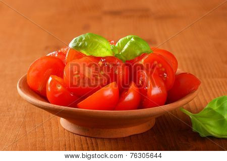 ceramic bowl of halved cherry tomatoes with leaves of basil