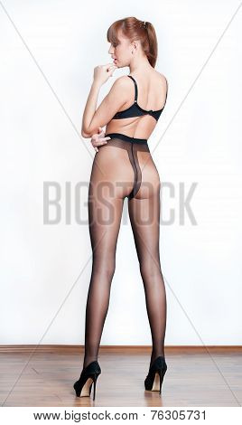 Attractive woman with long legs on high heels in black stockings posing. Back side view of woman