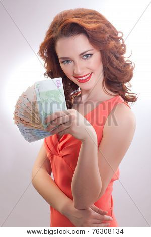 a beautiful woman in a pink dress with euro banknotes in the hands