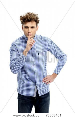 Young man making silence gesture