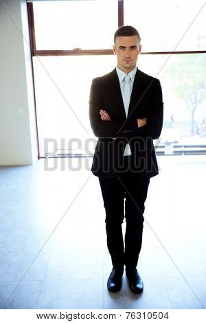 Full length portrait of a businessman standing with arms folded at office