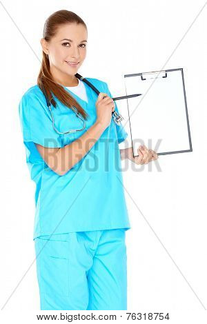 Attractive female doctor in blue scrubs pointing to a blank white page on a clipboard which she is displaying to the camera