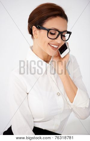 Attractive young businesswoman in glasses chatting on a mobile phone smiling as she listens to the conversation  over white