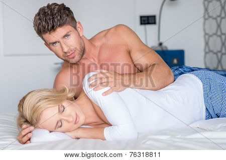 Loving romantic couple in bed with the man tenderly holding his wife as she enjoys a peaceful sleep looking at the camera