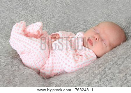 Newborn baby girl wearing a pink sleeper.
