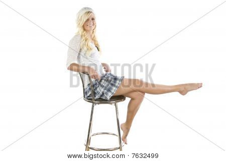 Girl In Blue Skirt On Chair Leg Up