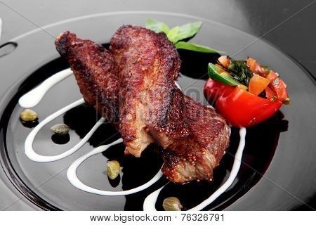 fresh red beef meat steak barbecue garnished vegetable salad sweet potato and basil on black plate over black wooden table with bbq sauce in sauce boat