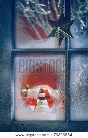Frosted window with Christmas decoration inside at night