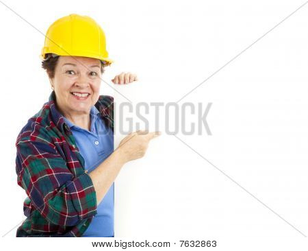Female Worker Points At Sign