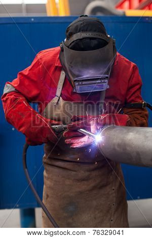 Welder in factory with protective equipment