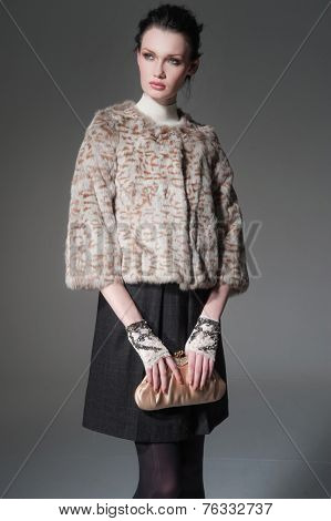 portrait of fashion model holding little purse posing on light background