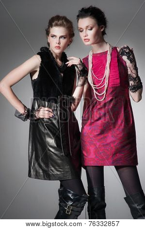 Young fashion two girl wearing black and red clothes on gray background