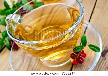Tea with lingonberry in glass cup on board
