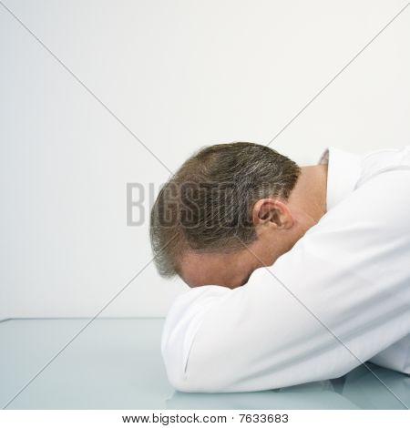 Empresario con la cabeza en el escritorio