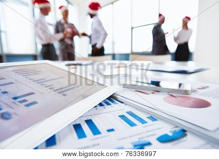 Close-up of papers, touchpad and cellphone at workplace on background of office workers in Santa caps interacting