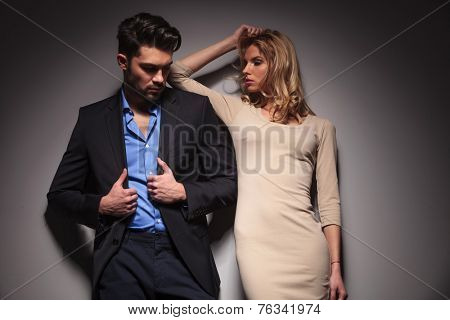 Handsome young fashion man looking down and fixing his jacket while his girlfriend is arrangeing her hair.