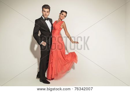 Handsome young elegant business man holding his lover while she is lifting one leg in the air, fluttering her dress.