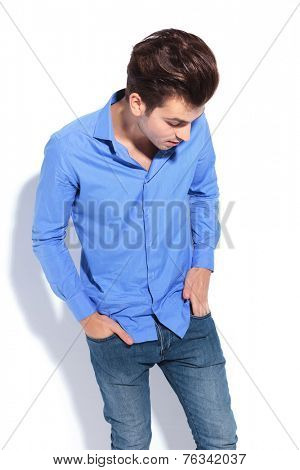 Fashion man looking down while putting his hand in pocket.