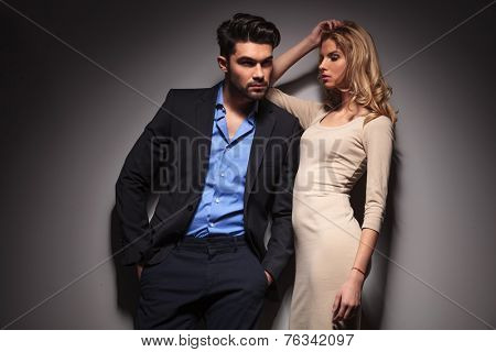 Attractive blonde fashion woman looking down while leaning her arm on her lover. The man is looking away and holding his hands in pockets.