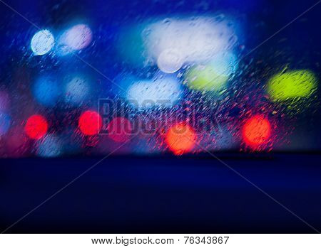 View from the car in rainy night, looking on blurry glowing cars lights through windscreen, automobile traffic in nighttime