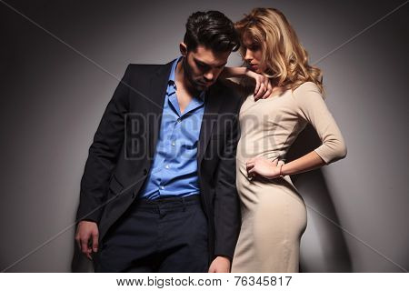 Beautiful blonde woman leaning on her lover while he is leaning on a grey wall, both looking down